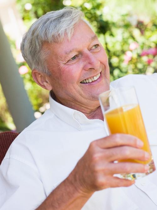 Senior man enjoying glass of juice